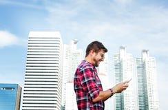 Ung man som använder bläddra det Smartphone begreppet royaltyfria foton