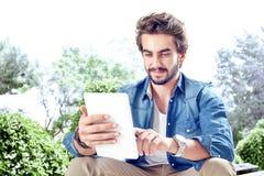 Ung man som använder den Digital minnestavlan Fotografering för Bildbyråer