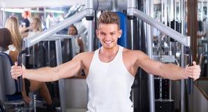 Ung man som använder den klipska maskinen i idrottshall Royaltyfria Foton
