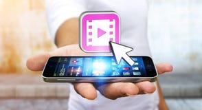 Ung man som använder den moderna mobiltelefonen för att hålla ögonen på videoen Arkivfoton