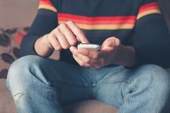 Ung man som använder den smarta telefonen Fotografering för Bildbyråer