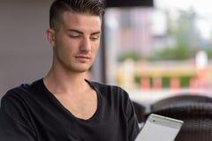 Ung man som använder digital minnestavladet fria, medan sitta royaltyfria foton