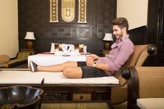 Ung man som använder en minnestavlaPC i ett asiatiskt hotellrum Royaltyfri Foto