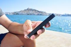 Ung man som använder en smartphone i den Ibiza staden, Spanien Arkivbilder
