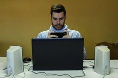 Ung man som använder hans mobil, minnestavla, bärbar dator och hörlurar royaltyfri fotografi