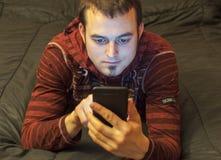 Ung man som använder hans mobiltelefon Arkivbild