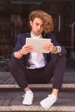 Ung man som använder minnestavladatoren på gatan Internet Royaltyfri Foto