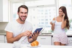 Ung man som använder minnestavlaPC på frukosten Arkivfoto