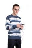Ung man som använder mobiltelefonen för att lyssna till musik Royaltyfri Foto