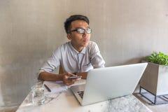 Ung man som använder mobiltelefonen och bärbara datorn och tänker på kontoret royaltyfri foto