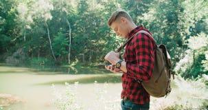 Ung man som använder smartphonen i en skog Arkivfoton