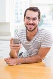 Ung man som använder smartphonen, medan ha kaffe Arkivbild