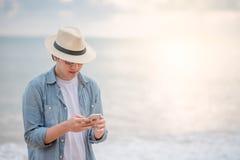 Ung man som använder smartphonen på stranden Royaltyfri Foto