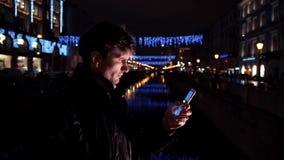 Ung man som använder smartphonen som står ensam det fria på natten på den upptagna stadsgatan arkivfilmer