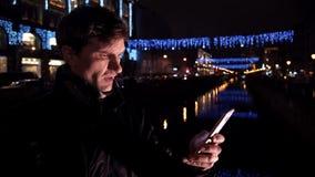 Ung man som använder smartphonen som står ensam det fria på natten på den upptagna stadsgatan lager videofilmer