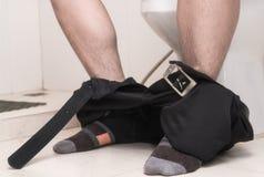 Ung man som använder toaletten och tar bort hans byxa ner på golvet Royaltyfria Bilder
