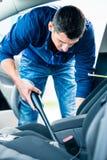 Ung man som använder vakuumet för att göra ren inre av en bil fotografering för bildbyråer