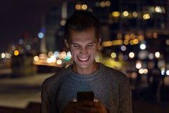 Ung man som anv?nder hennes smartphone under natten stadsljus som bakgrund royaltyfri bild