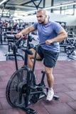 Ung man som anv?nder motionscykelen p? idrottshallen Konditionman som anv?nder luftcykeln f?r cardio genomk?rare p? crossfitidrot arkivbild