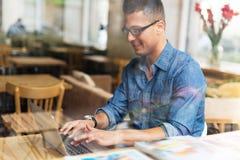 Ung man som använder bärbara datorn på kafét Arkivfoto
