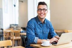 Ung man som använder bärbara datorn på kafét Royaltyfri Bild