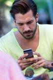 Ung man som använder hans mobiltelefon i gatan Arkivbild