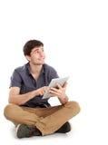 Ung man som använder minnestavlaPC Arkivfoto