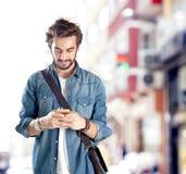 Ung man som använder mobiltelefonen i gata Royaltyfria Bilder