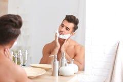 Ung man som applicerar raka den near spegeln för skum arkivfoto
