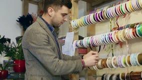 Ung man som arbetar i blomsterhandel och dekorativ tillbehör arkivfilmer