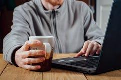 Ung man som arbetar med bärbara datorn och kaffe Royaltyfri Foto