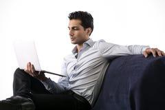 Ung man som arbetar på bärbar datordatoren, medan sitta på soffan. Arkivbilder