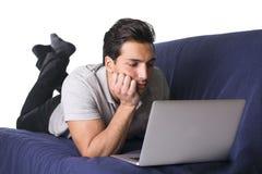 Ung man som arbetar på bärbar datorPC:N Arkivfoto