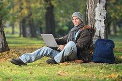 Ung man som arbetar på bärbara datorn som placeras av ett träd i PA Royaltyfri Fotografi