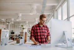 Ung man som arbetar på datoren i modernt kontor arkivbilder