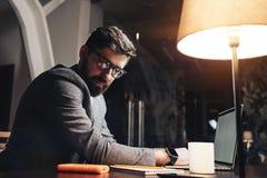 Ung man som arbetar på det moderna kontoret för natt suddighet bakgrund Skäggig chef som använder bärbar dator- och pappersnotepa royaltyfria foton