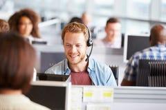 Ung man som arbetar på en dator i en call center fotografering för bildbyråer