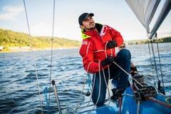 Ung man som arbetar på seglingskeppet, aktiv livsstil, sommarsportbegrepp royaltyfri bild