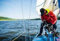Ung man som arbetar på seglingskeppet, aktiv livsstil, sommarsportbegrepp fotografering för bildbyråer