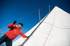 Ung man som arbetar på seglingskeppet, aktiv livsstil, sommarsportbegrepp royaltyfria foton