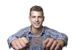 Ung man som av visar hans körkort Royaltyfri Bild
