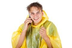 Ung man som bär en gul regnrock som kallar en taxi Royaltyfria Bilder