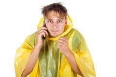 Ung man som bär en gul regnrock som kallar en taxi Arkivfoto