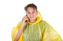 Ung man som bär en gul regnrock som kallar en taxi Fotografering för Bildbyråer