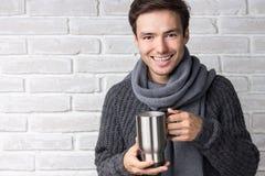 Ung man som bär en halsduk som dricker te och att le Arkivfoto
