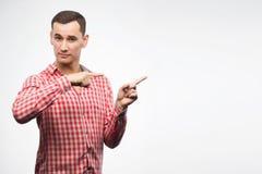 Ung man som bär rutiga röda skjortapunkter med hans finger till Arkivfoton