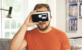Ung man som bär VR-virtuell verklighetskyddsglasögon Fotografering för Bildbyråer