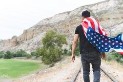 Ung man som b?r en amerikanska flaggan p? Juli 4th arkivfoto