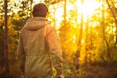 Ung man som bara står i skogen som är utomhus- med solnedgångnaturen på bakgrund