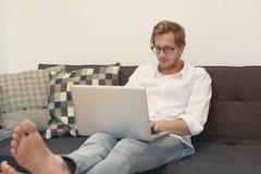 Ung man som barfota sitter på soffan med bärbara datorn Royaltyfri Foto